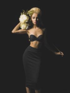 Elegant blonde with white peony on black background